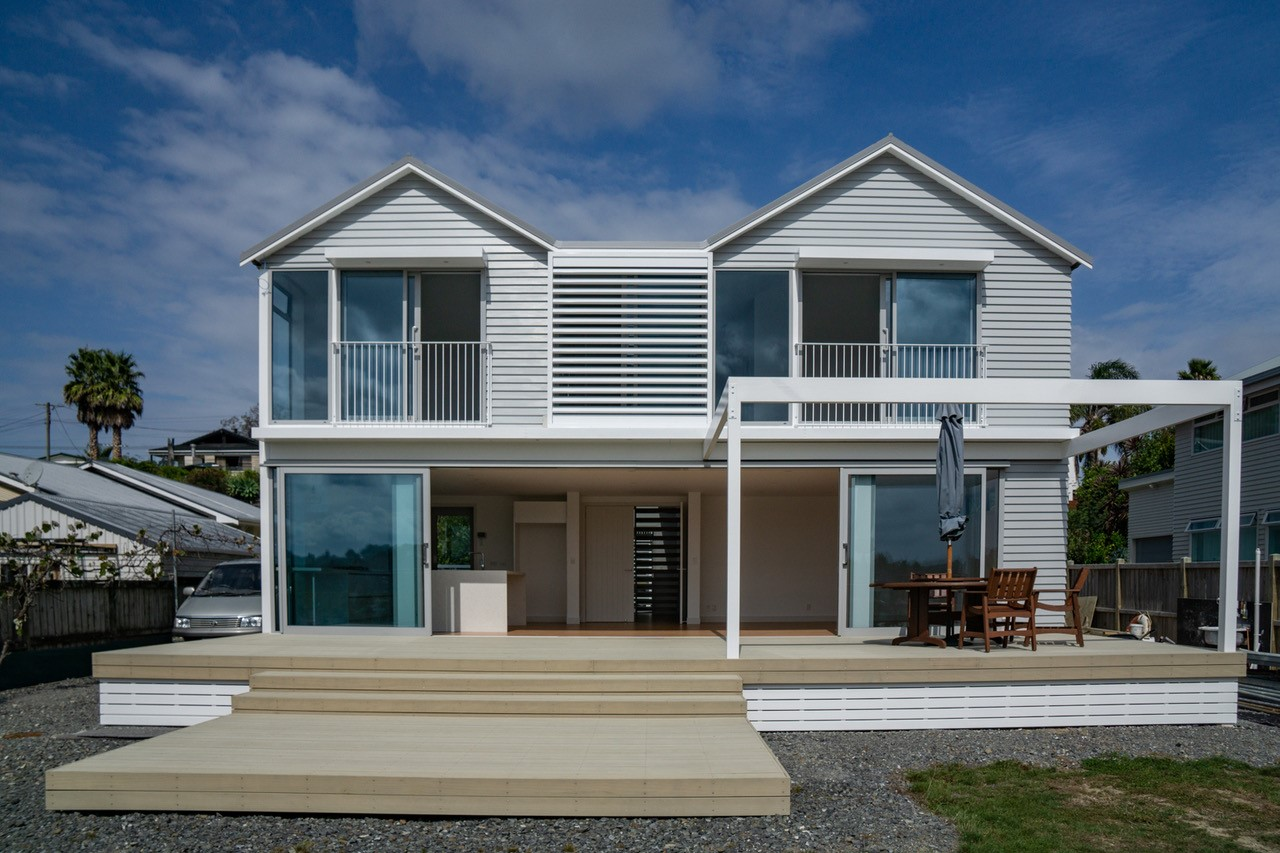 two-level residential home painted white with timber deck