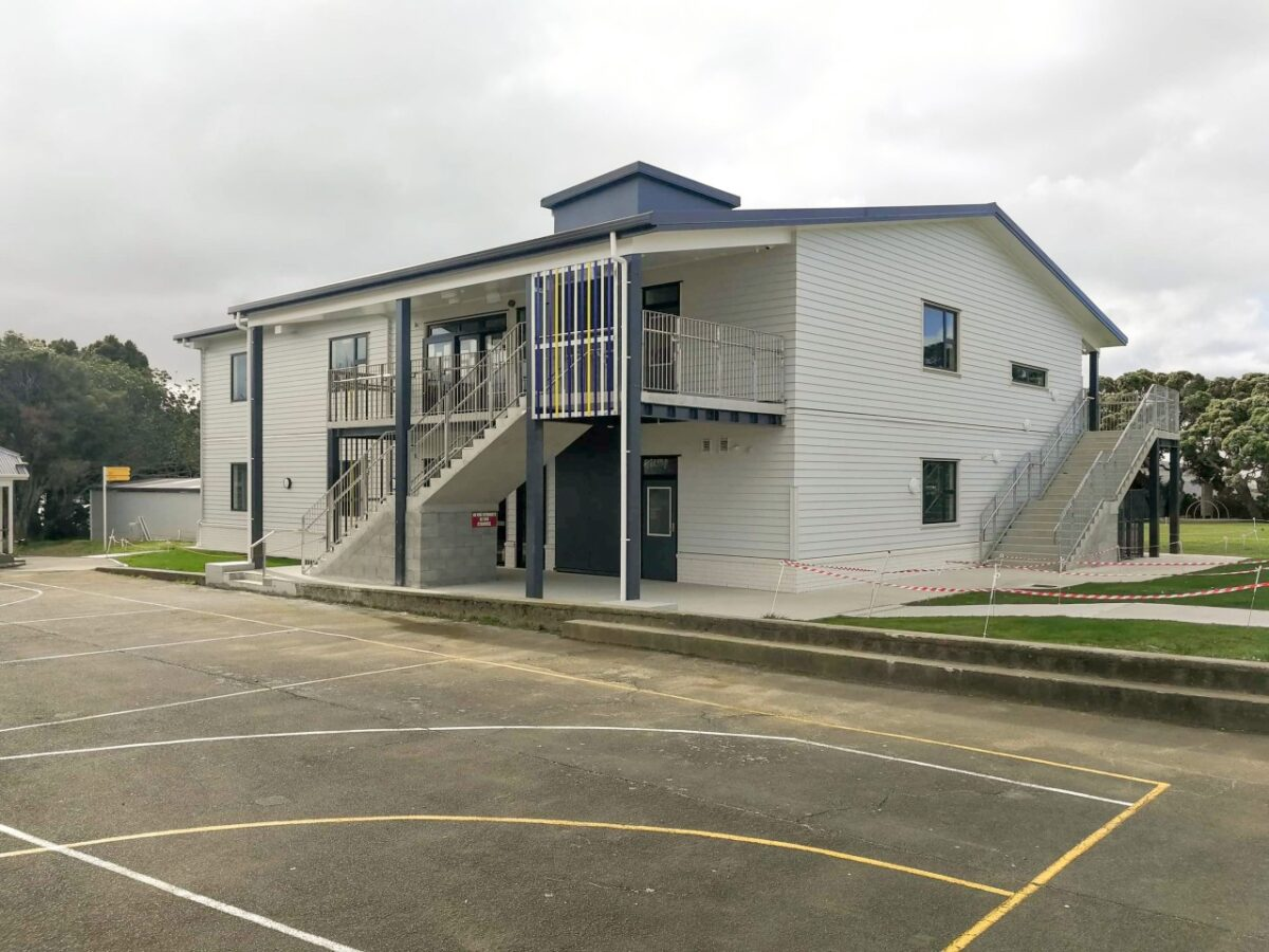 picture of school building in front of a schools court. The building is two levels painted white with stairs going up to the second level in fron.